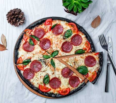 black pepperoni pizza with tomato and basil Stok Fotoğraf