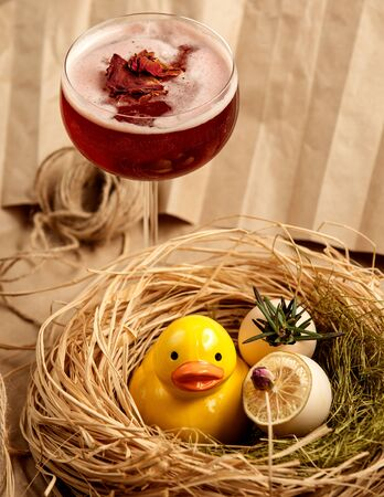 red cocktail garnished with dried rose petals next to ceramic