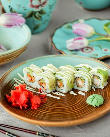 plate of sushi rolls covered avocado and cream stripes