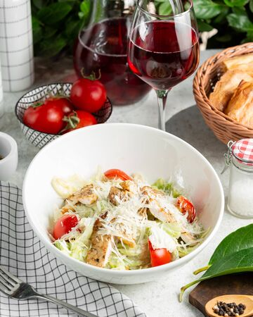 caesar salad with tomato, lettuce, served with wine