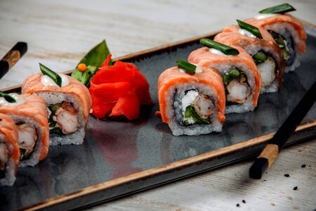 close up of sushi rolls covered with salmon, served with