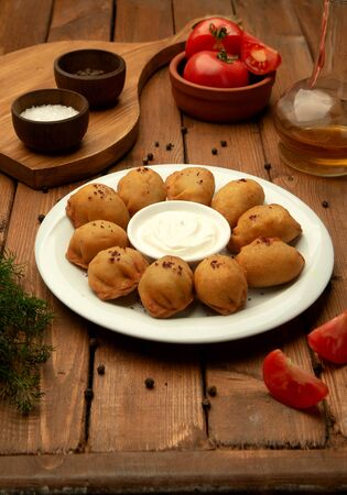 fried pelmeni dumplings served with yoghurt