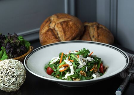 fresh vegetable salad with arugula, cheese, walnut, carrot, cucumber and