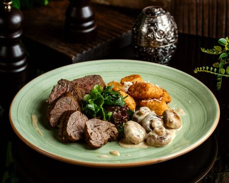 beef steak pieces served with mushrooms in cream sauce, herbs