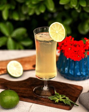 a glass of lime juice garnished iwth ice and lime