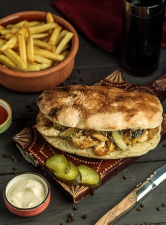 chicken doner in bread stuffed with pickled cucumber served with