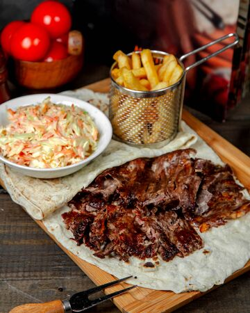 meat doner with french fries on wooden board