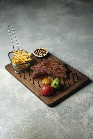 medium raw steak with side fries and vegetables