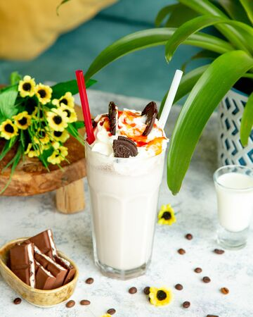milkshake topped with whipped cream caramel and cookies Stok Fotoğraf - 134747547