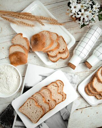 sliced white bread and wheat branches Stok Fotoğraf - 134747681