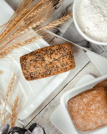 loaf of bread topped with poppy and wheat branches Stok Fotoğraf - 134747691