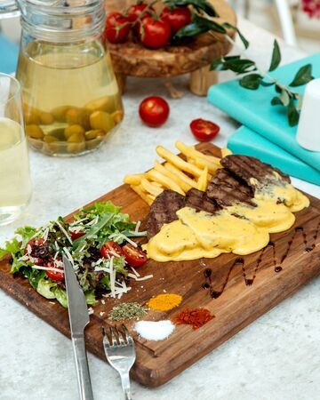 roasted meat in melted cheese and fries with salad