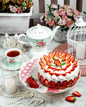 strawberry cake ornated with sliced strawberries and a black tea Stok Fotoğraf