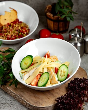 vegetable salad topped with sliced cheese and cucumber
