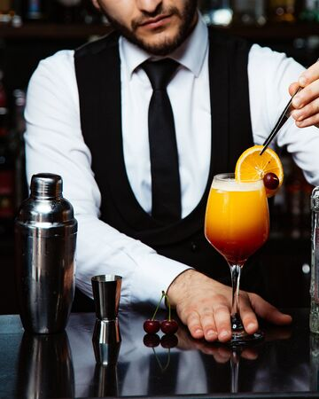 bartender places orage slice on cocktail Stok Fotoğraf