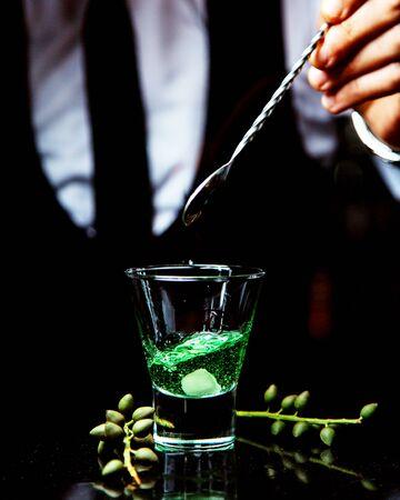 bartender dropped a sugar into a shot of absinth