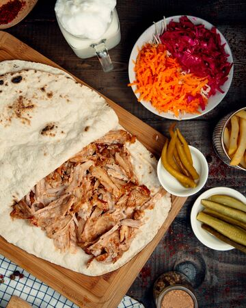 chopped pieces of chicken in pita bread and pickles Standard-Bild - 134963065