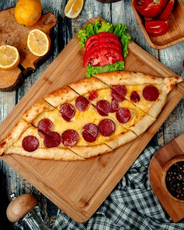 sliced pide with sujuk on a wooden board Stock Photo