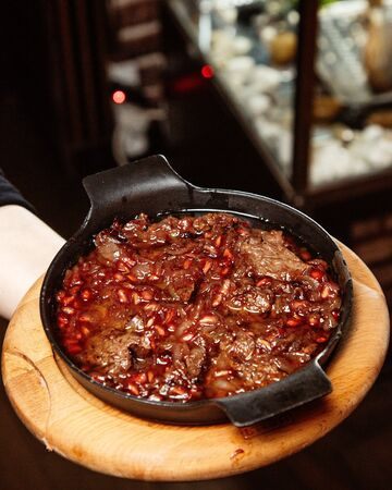 lamb stew with onion and pomegranate seed in cast iron Stock Photo