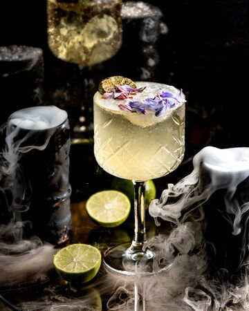 a crystal glass of lime cocktail garnished with flower petals Stock Photo
