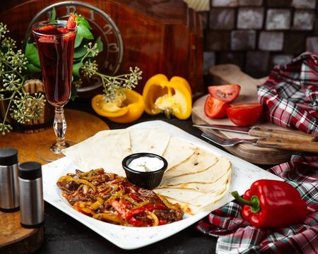 a platter of beef fajitas served with flatbread and sauce Stock Photo
