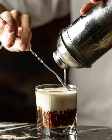 bartender pours cream into iced coffee with the help of the spoon Imagens