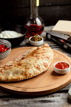 pizza calzone on wooden board