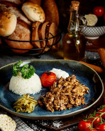 fried meat with mushrooms and rice