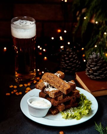 garlic toasts with sauce and glass of beer