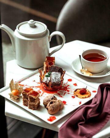 various cakes and glass of black tea 版權商用圖片 - 144710738