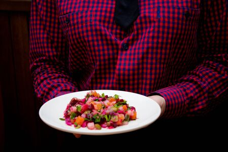 a person holds vegetable salad
