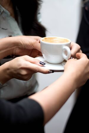 a person holds a cup of cappuccino 版權商用圖片