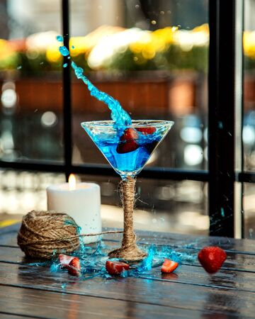 strawberries splashed into a martini glass