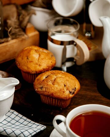 two muffins with raisins served with black tea