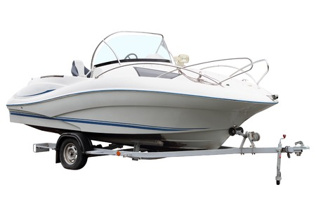 motor boat: White motor boat loaded on the trailer for transportation.