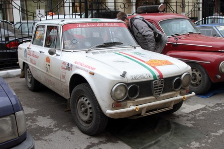 next stage: PERM, RUSSIA - JUNE 29, 2016: Rally of retro-cars Peking-Paris 2016 , June 29, 2016 in Perm, Russia. White Alfa Romeo Giulia Super is in the city after the next stage.