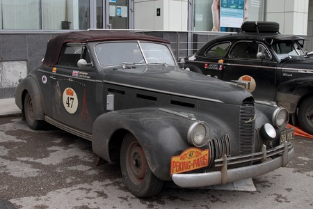 next stage: PERM, RUSSIA - JUNE 29, 2016: Rally of retro-cars Peking-Paris 2016 , June 29, 2016 in Perm, Russia. Cadillac La Salle is near the hotel after the next stage.