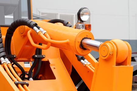 hinge joint: Hydraulic hoses and piston of a modern tractor.