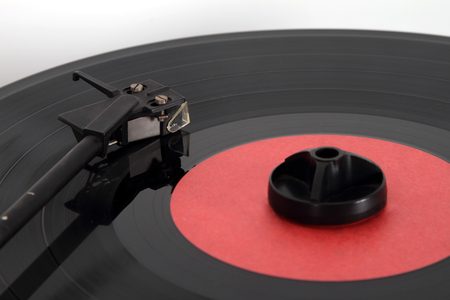 Pickup and a vinyl disk with a cleaning pad lying on it to remove dust. Focus on the pickup head. Stockfoto