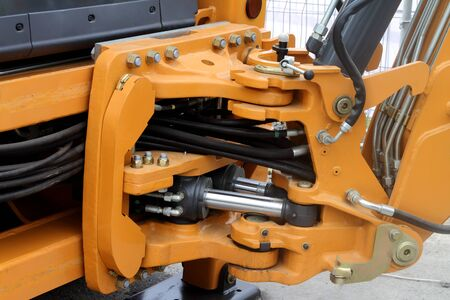 Swivel and hydraulic hoses on a yellow tractor. 스톡 콘텐츠