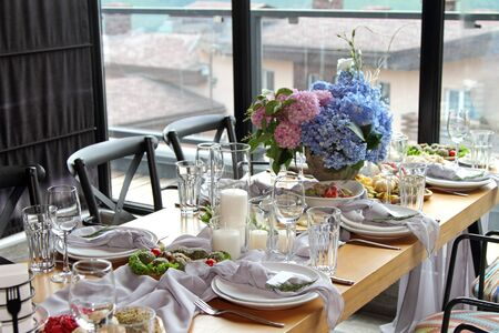 The festive table with traditional Georgian dishes is decorated with flowers.