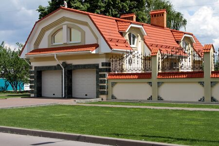 Green lawn in front of a modern garage with two entrances.