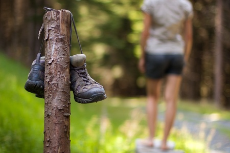 Abandoned hiking shoes with a woman walking bare feet Banque d'images