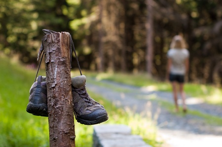 Abandoned hiking shoes with a woman walking bare feet Stock Photo