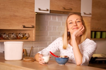 happieness: Young woman having a bowl of cereal