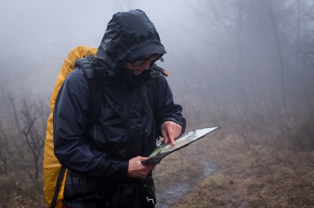 Young woman reading a map in the misty evening