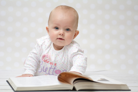 Baby girl lying on the belly reading a book and looking at the camera Stock Photo