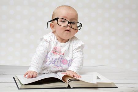 大きな本を横になっている眼鏡の女の子のかわいい赤ちゃんの面白い肖像画