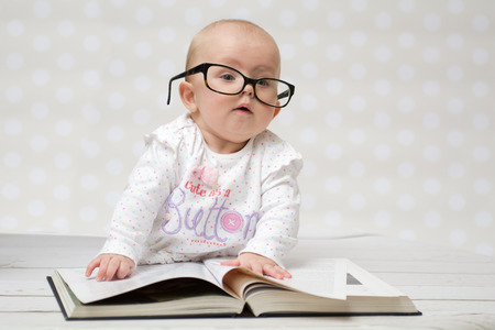 Funny portrait of a cute baby girl in glasses lying over a big book