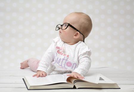 Drôle portrait d'une petite fille mignonne dans des verres couché sur un grand livre